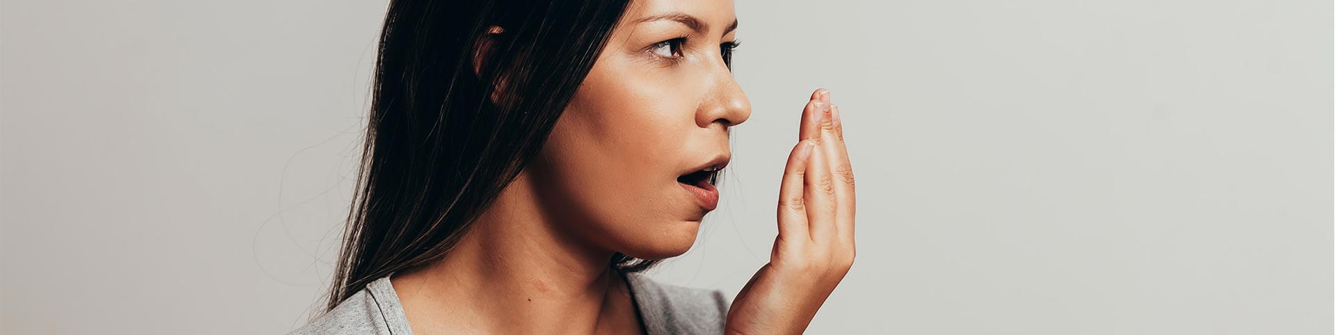 Frau die sich die Hand vor den Mund hält, um zu überprüfen, ob Sie Mundgeruch hat